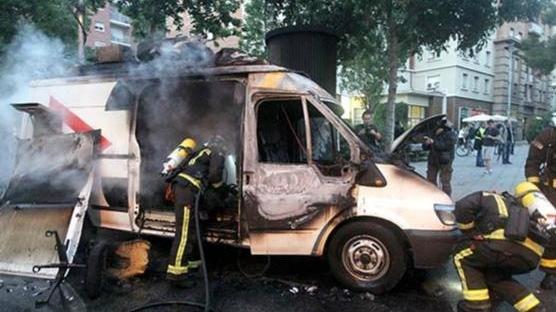 Un grup d'incontrolats cala foc a una unitat mòbil de TV3 que cobria la informació de Can Vies. (Foto: Xavier Gómez)