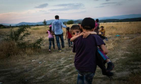 Un jove refugiat porta en braços al seu germà a prop d'Eidomeni (Grècia) | Foto: ACNUR / Andrew McConnell